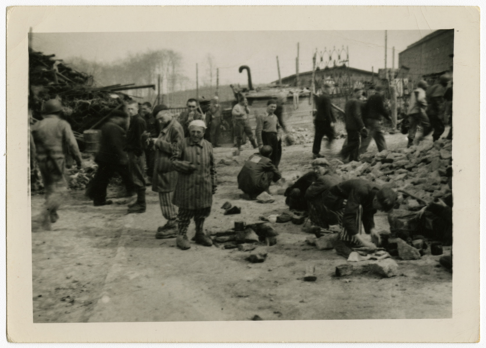 Survivors gather on the grounds of [what is probably the Buchenwald concentration camp.]