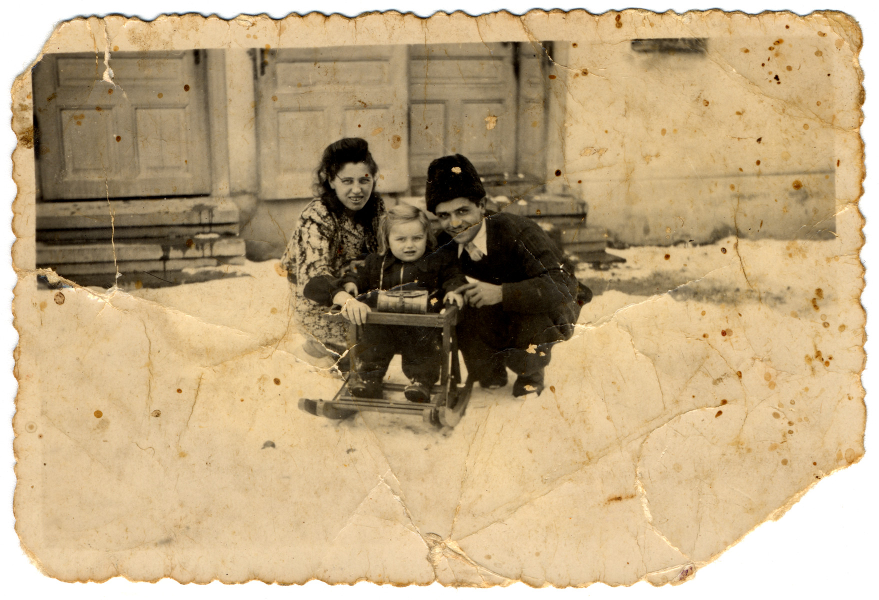 Yevgeniy and his first wife Rozsi play with their young son in the snow.
