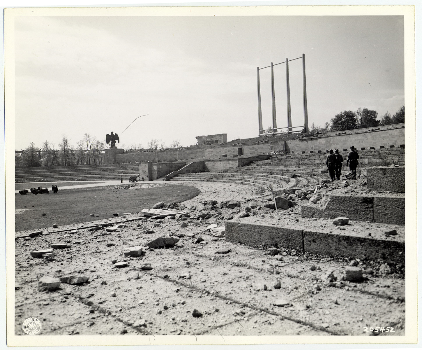 Soldiers walk among the rubble of Berlin's Olympic stadium. The Nazi eagle is still standing.