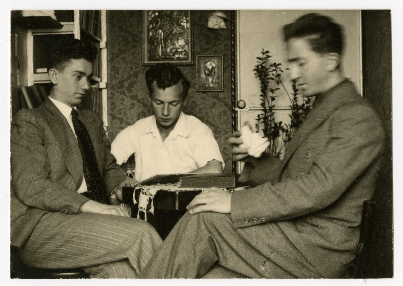Mendel Grosman (right) sits in a parlor with two friends.