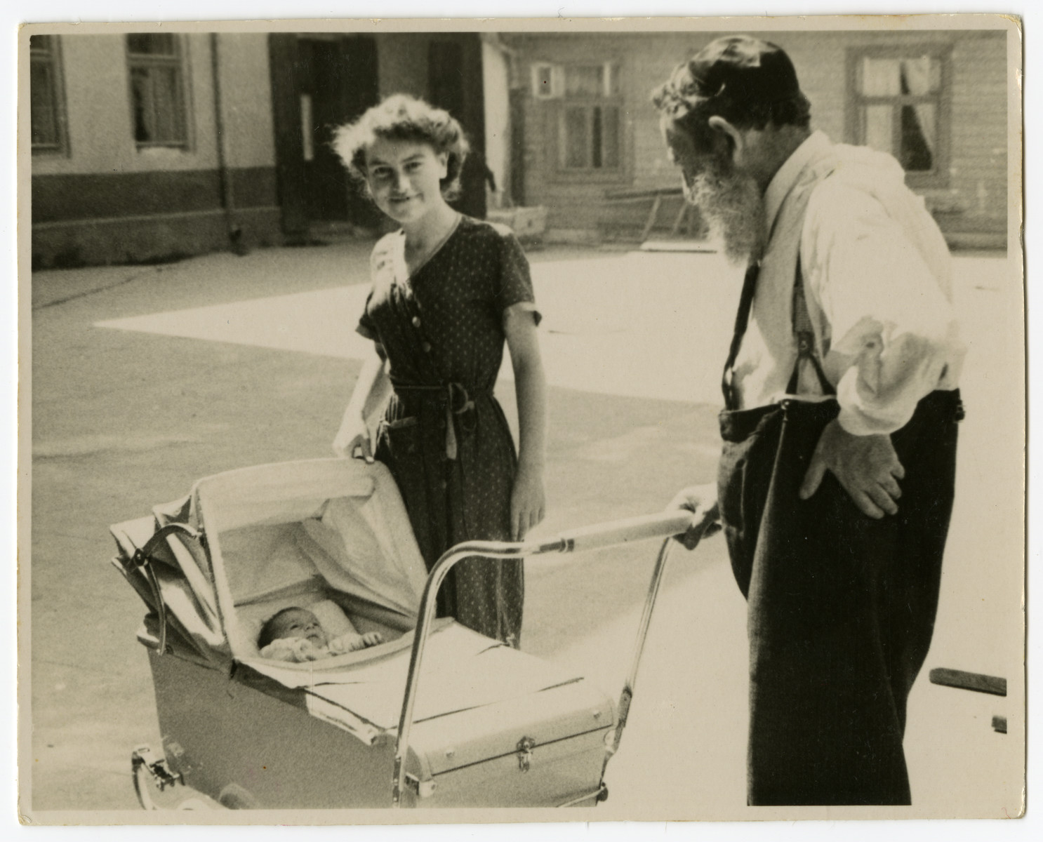 Shmuel Dawid Grosman pushes his grandson in a baby carriage while his younger daughter Ruszka looks on.