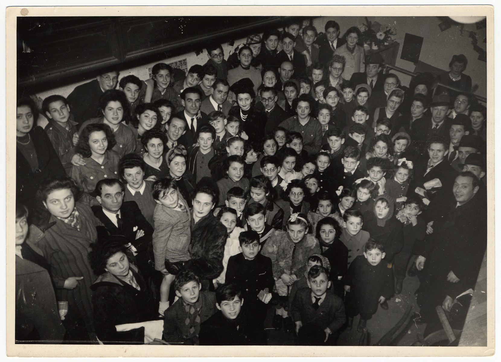 Belgian Jews gather for a holiday celebration after liberation.  Among those pictured Moshe Werber being held in the arms of Mrs. Flam.  His mother, Shifra Werber, is diagonally behind him; next to her is the Hebrew teacher Faivel Blank, Abush Werber, Fela Perelman and Israel Tabakman.  Lola Pomerantz is at the back, left.Jacques Silberman is pictured to their left.
