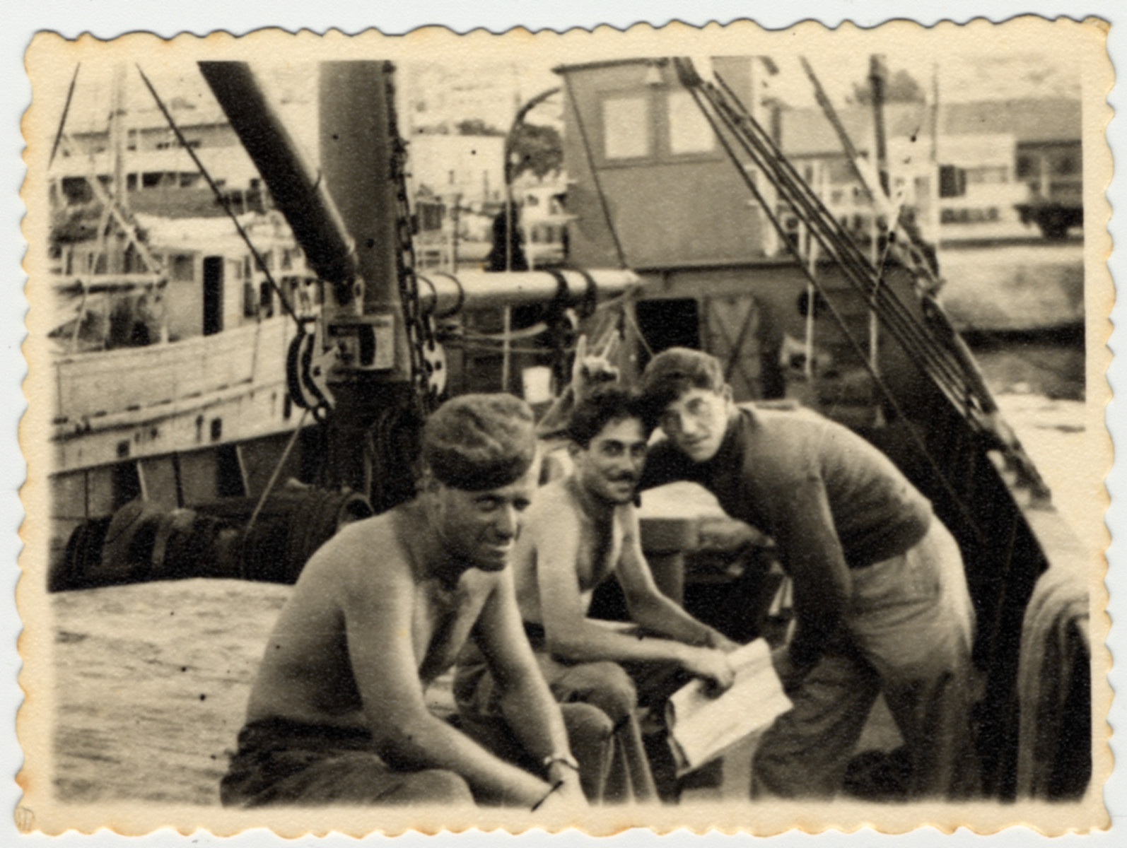 Three crew members of the SS Hannah Szenes relax on a dock in Haifa harbor.  Myron Goldstein is leaning over on the far right.