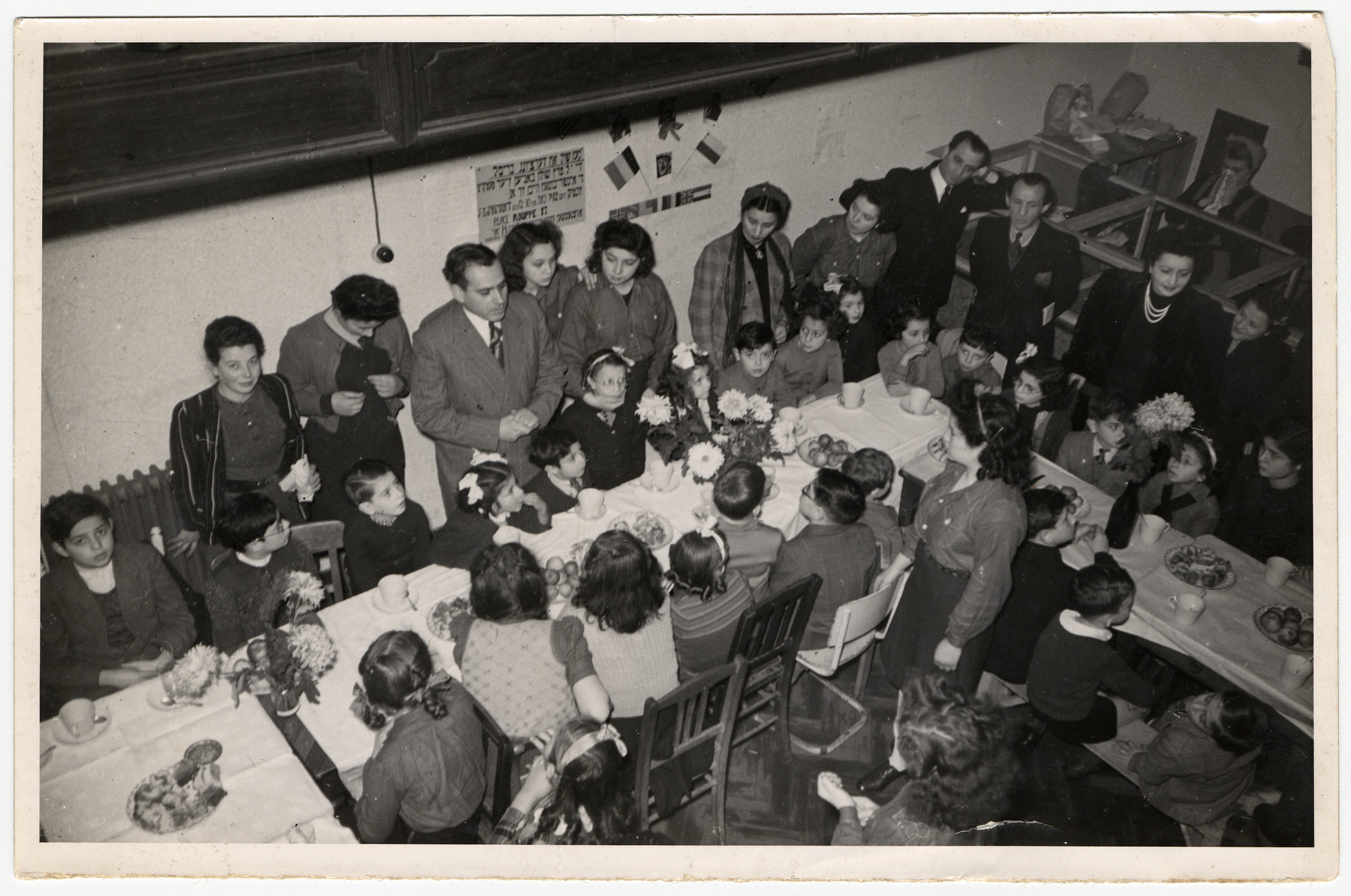 Children in a postwar children's home gather around long tables set with fruit and decorated with flowers.  Hebrew signs hang on the walls.  Among those pictured is Fela Perleman (standing second from the left).