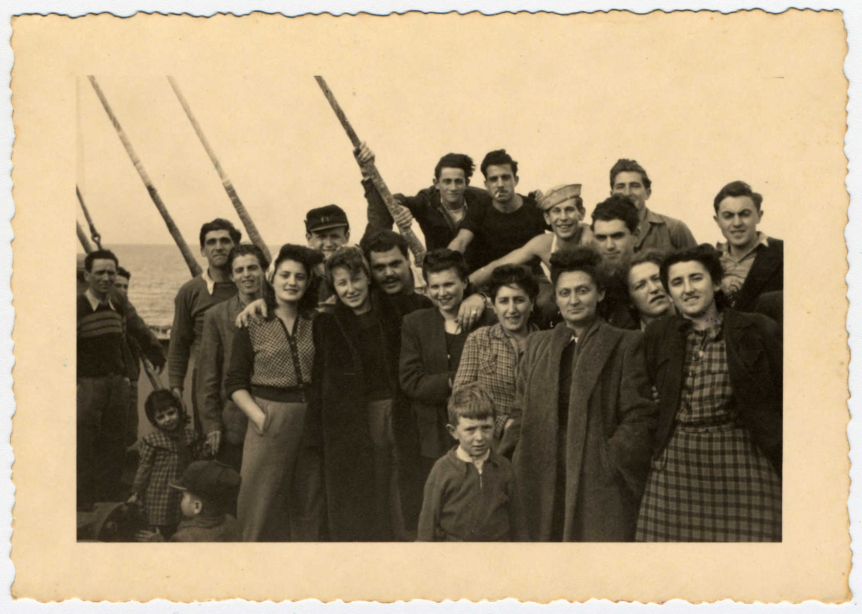 New immigrants gather on the deck of [what probably is] the Galila while en route to Israel from Romania.  Among those pictured are Avraham Heeres (third from the right in the white cap).