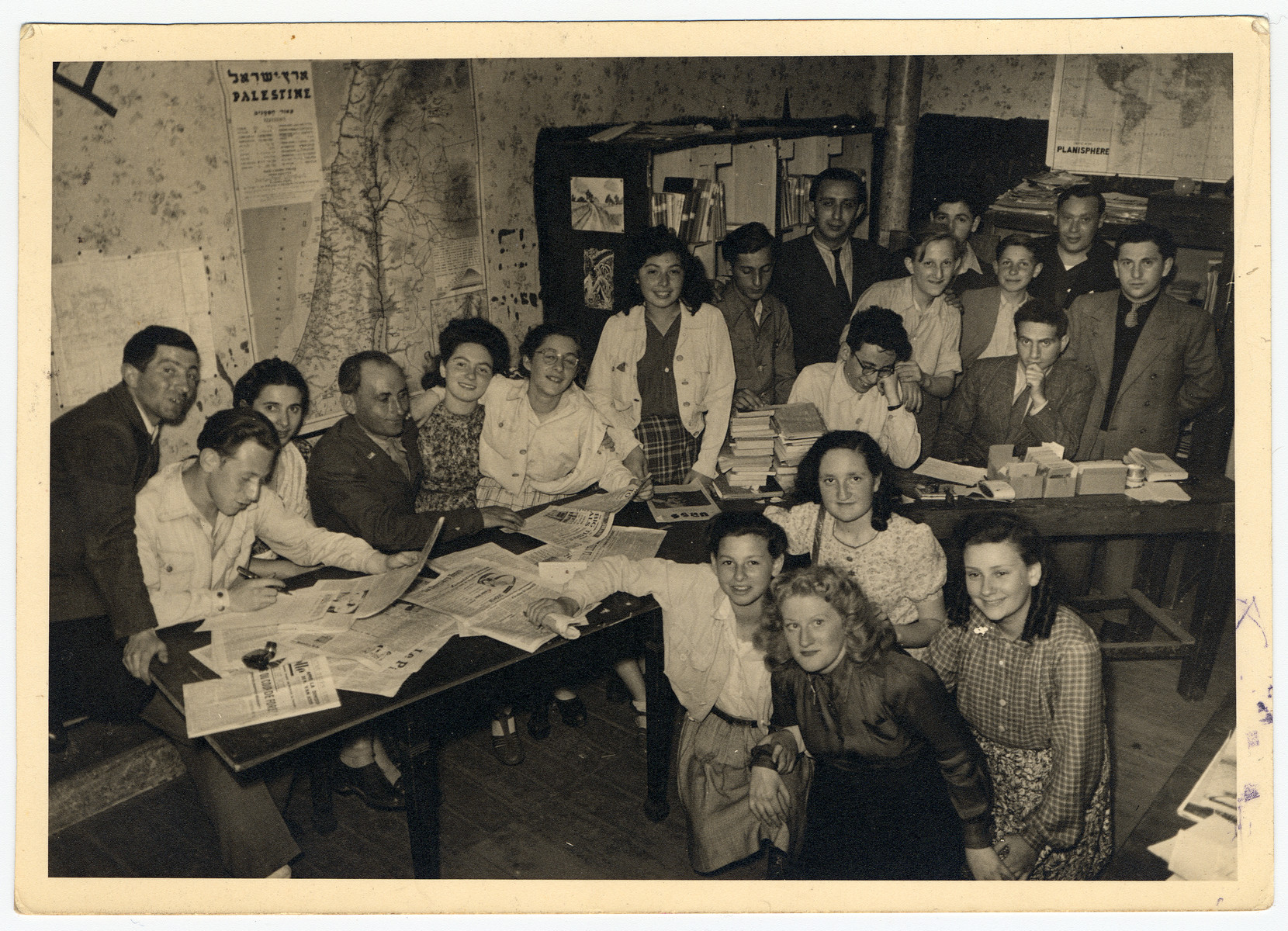 A group of Belgian Zionists gathers after the war in a room decorated with maps of Israel and filled with newspapers and books.