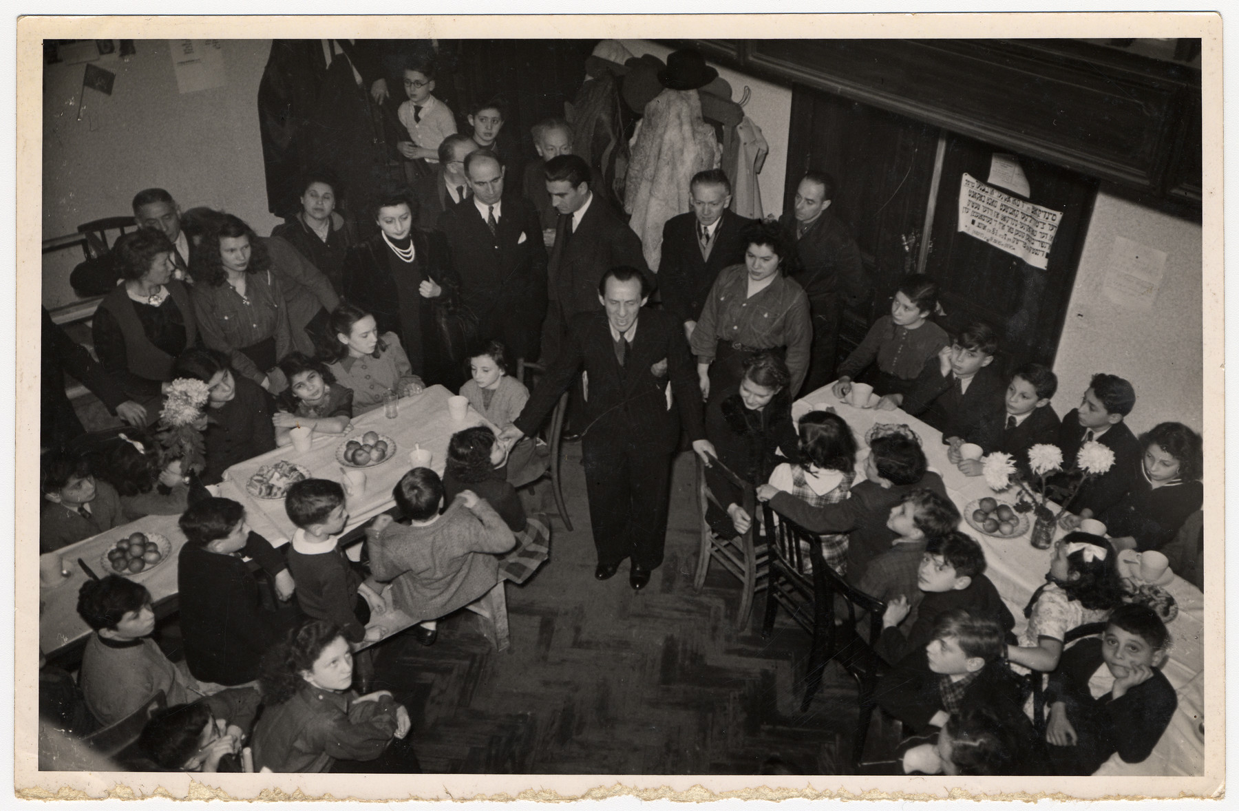 Children in a postwar children's home gather around long tables set with fruit and decorated with flowers.  Hebrew signs hang on the walls.  Among those pictured is Fela Perleman (standing center wearing pearls).