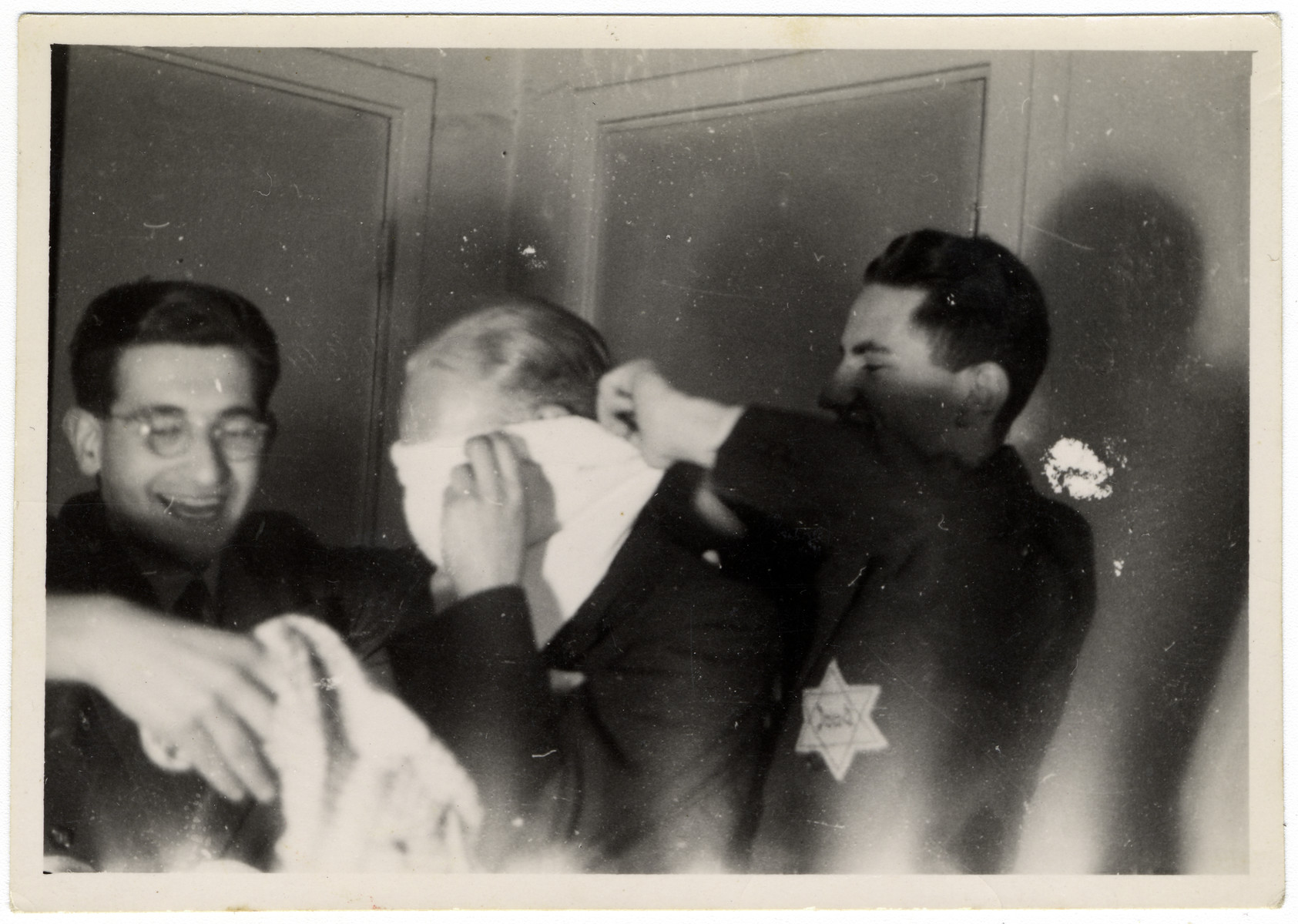 Jewish teenagers play a game with a blindfold at a party hosted by Rudy Acohen (left).  Shortly thereafter he was arrested in a reprisal action and sent to Auschwitz where he perished.