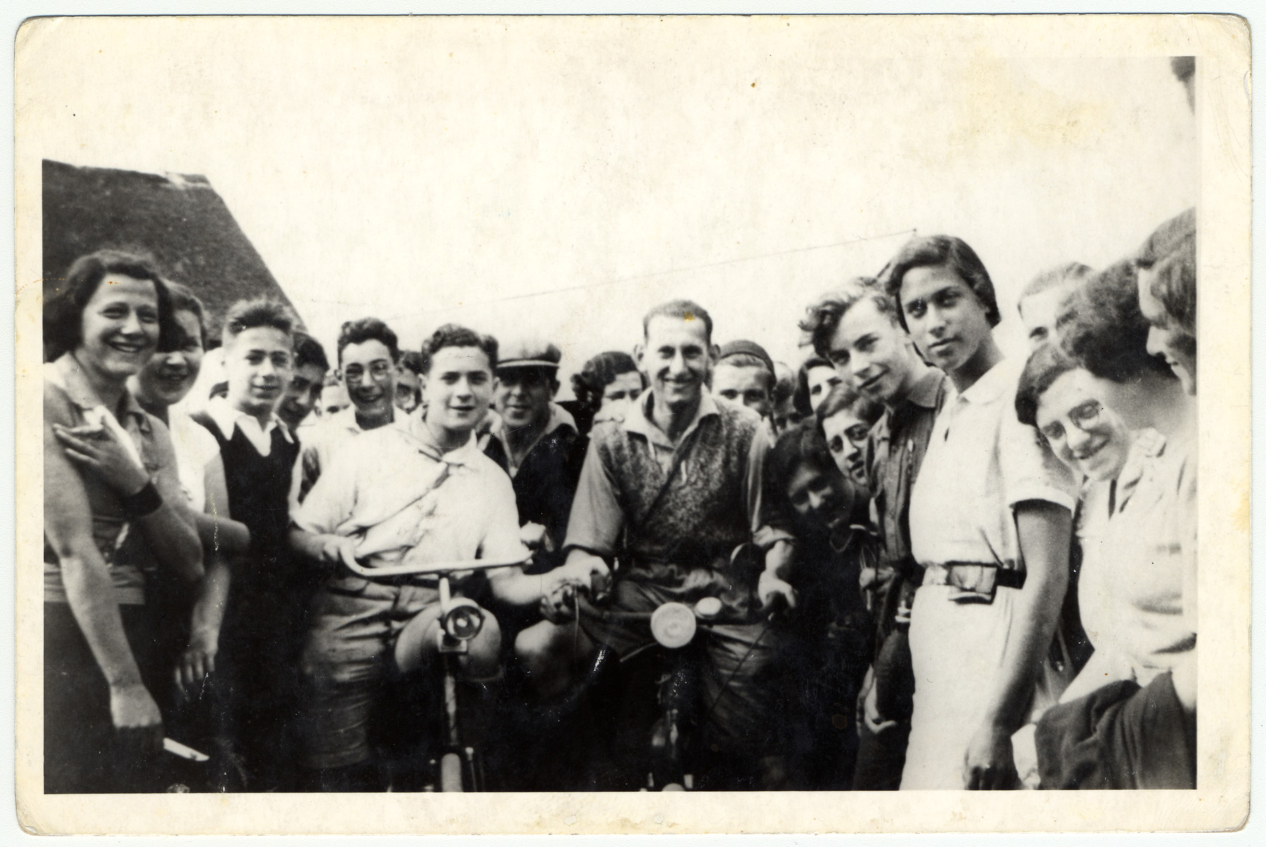 Group portrait of Zionist youth in a hachshara in The Netherlands.  Jacob Polak is pictured in the center right on a bicycle.
