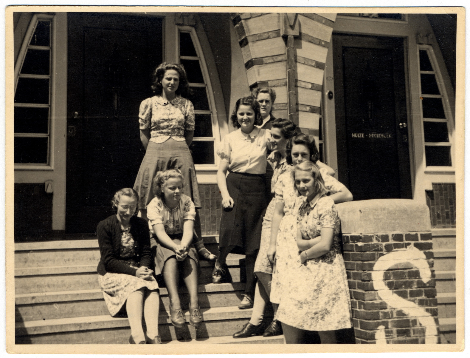 Girls from the graduation class of the Dutch Montessori Lyceum stand on the exterior steps of the school shortly after the German invasion of Holland.  The painted S stands for shelter.    Ina Soep is third from the left on the bottom row.