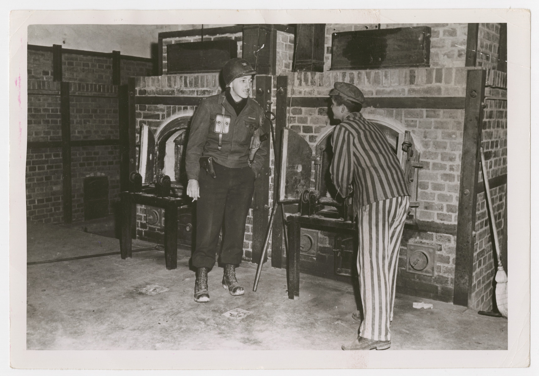 """A Dachau survivor shows the crematoria to an American soldier.   The original Signal Corps caption reads, """"Dachau atrocity camp a former prisoner freed when 7th U.S. Army troops  [?]rated the infa[?], shows [?] crematory furn[?]  [?]ol  Walter O'Brien whose men [?]red the camp."""
