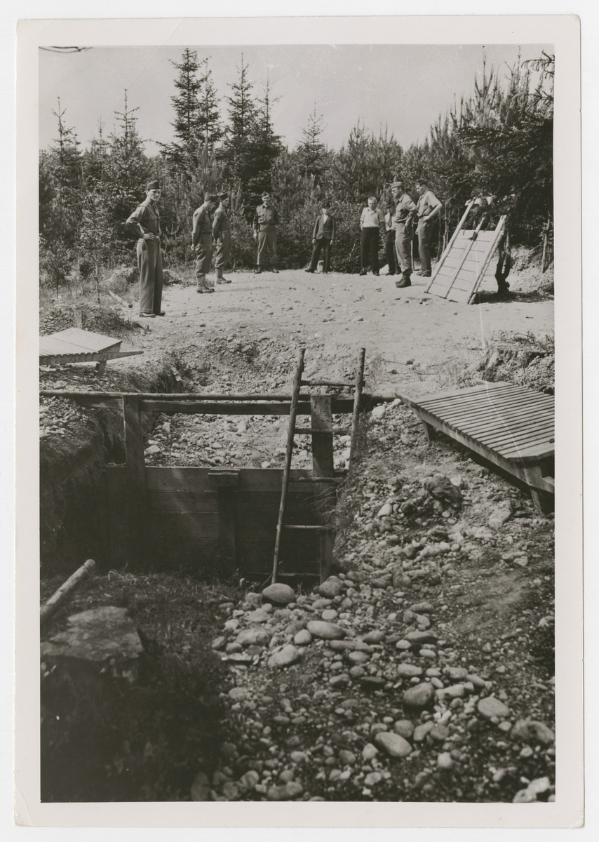 "American soldiers view a mass grave near Waldlager 11.  The original Signal Corps caption reads, ""Part of the mass grave [?]ned by the Germans near Waldlager 11. This is a smaller part of the ""L"" shaped grave. It is believed to be 50' deep and about 7' wide. Prisoners estimate that over 9000 are buried in it."""