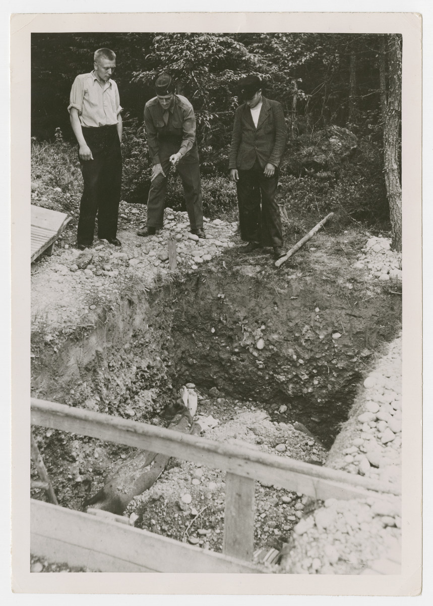 "A war crimes investigator and Russian former prisoners view a mass grave.  The original Signal Corps caption reads, ""Lt. Melvin Barkas, war crimes investigator with XV Corps, and 2 Russian  prisoners look into the mass grave near Waldlager 11. The grave is believed to be about 50' deep and is reputed to contain 9,000 bodies."""