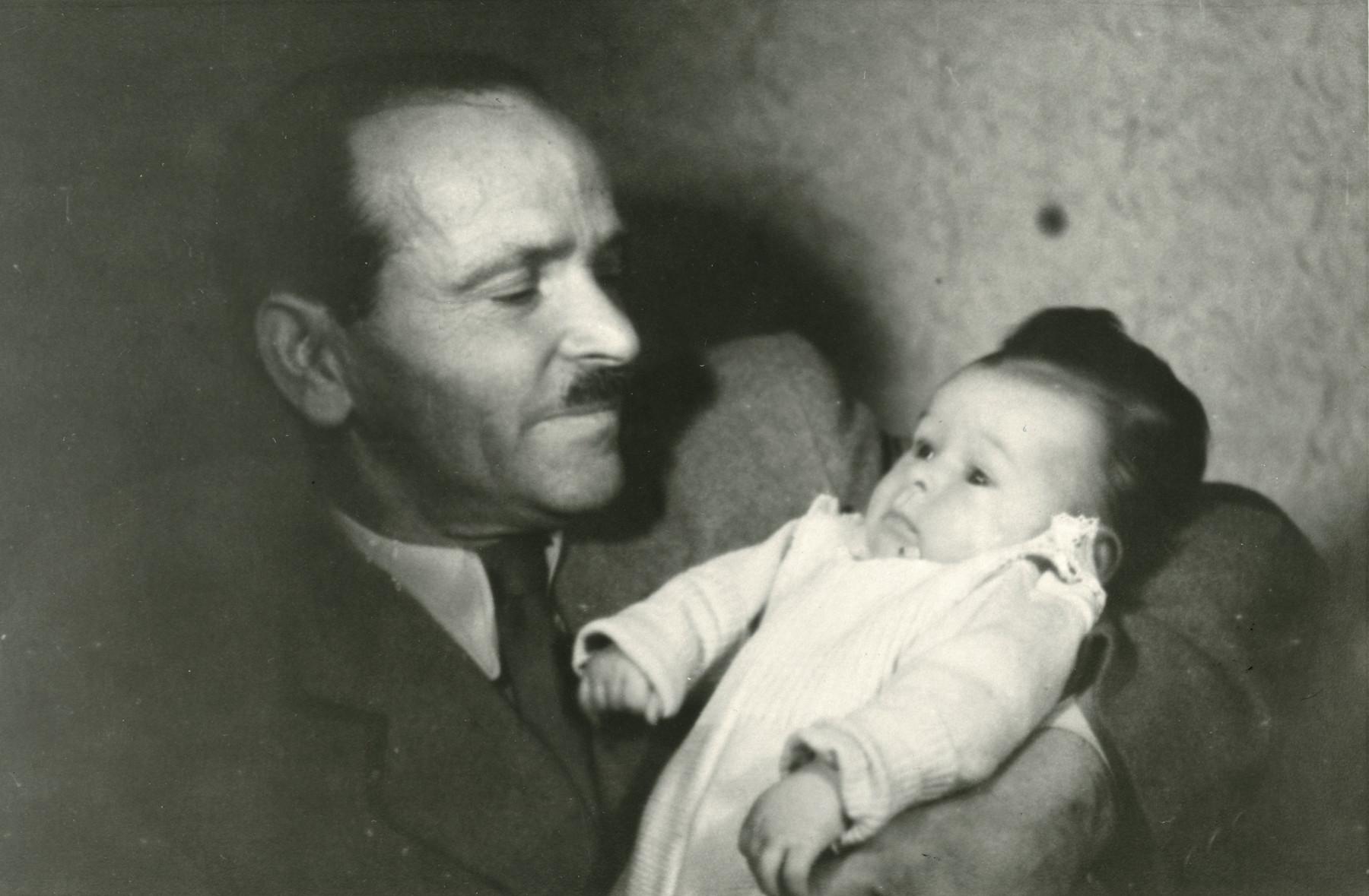 Avraham Bernat Koviliak holds his infant daughter Sara in his arms.