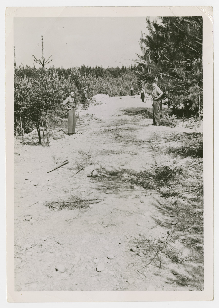 "American soldiers view mass graves near Muehldorf.  The original Signal Corps caption reads, ""Part of the mass grave the Germans had near Walderlager 11. The longer part of the ""L"" shape is about 200 feet long, 7' wide and is believed to be 50' deep. Prisoners claim that 9000 are buried in it."""