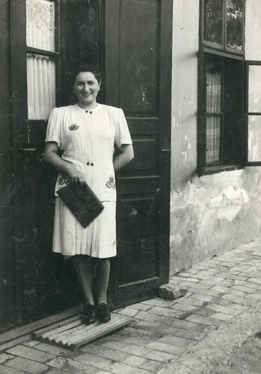 Eva (Hava) Weiss stands in front of the entrance to a building in the late 1930s.