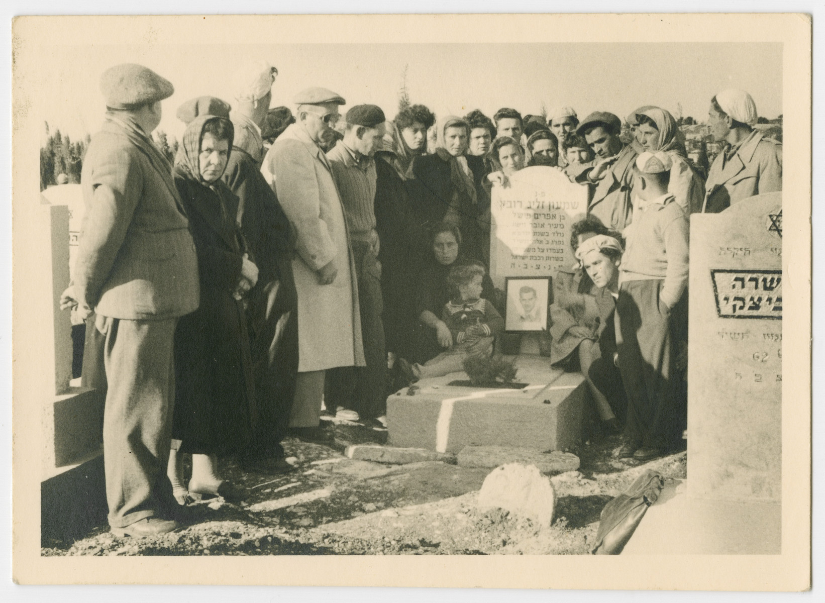 Men and women gather around a grave in a cemetery in Israel.