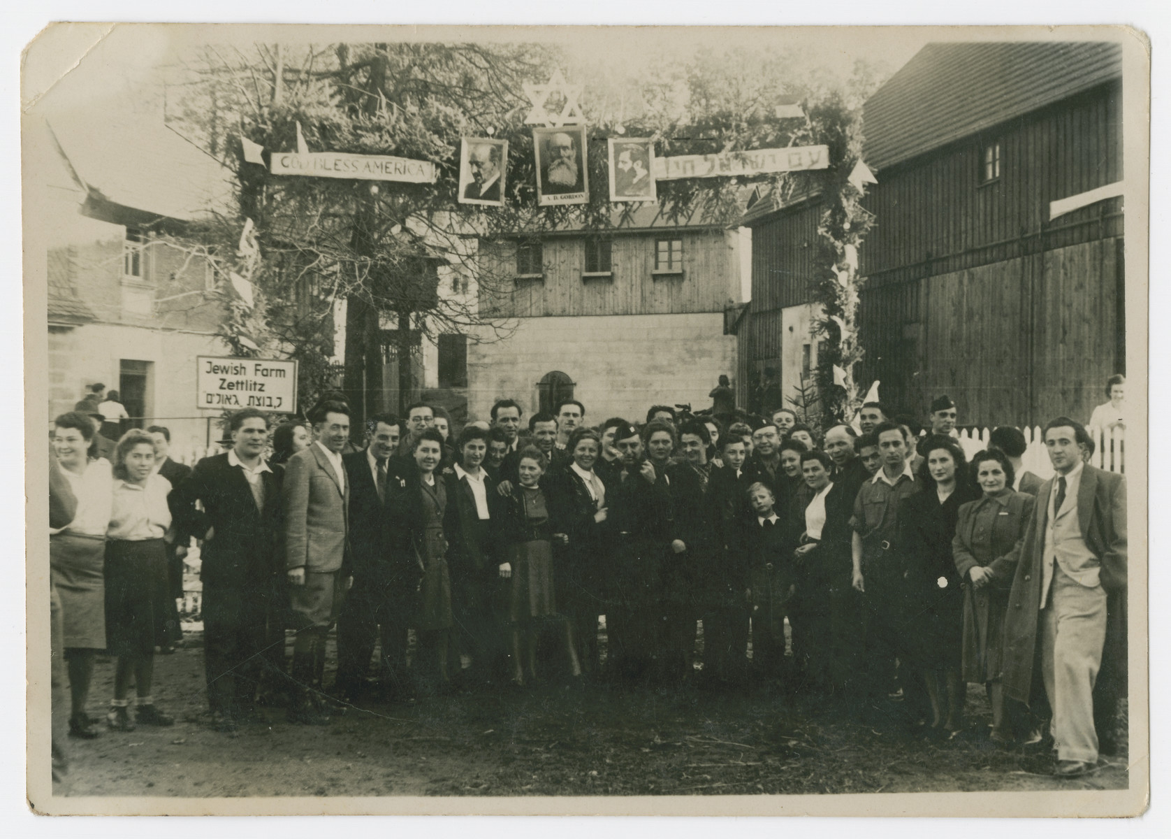 Group portrait of young Zionists in the Zeittlitz training farm posing underneath posters of Weizmann, Gordon and Herzl.