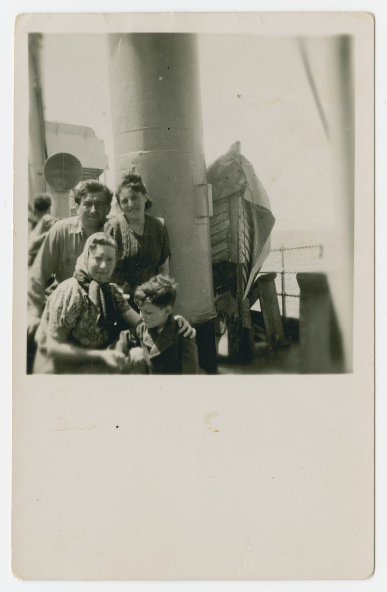 A group of Jewish displaced persons pose on the deck of a ship [probably en route to Palestine].  The couple in the back were identified in another photograph as Sala and Dawid.