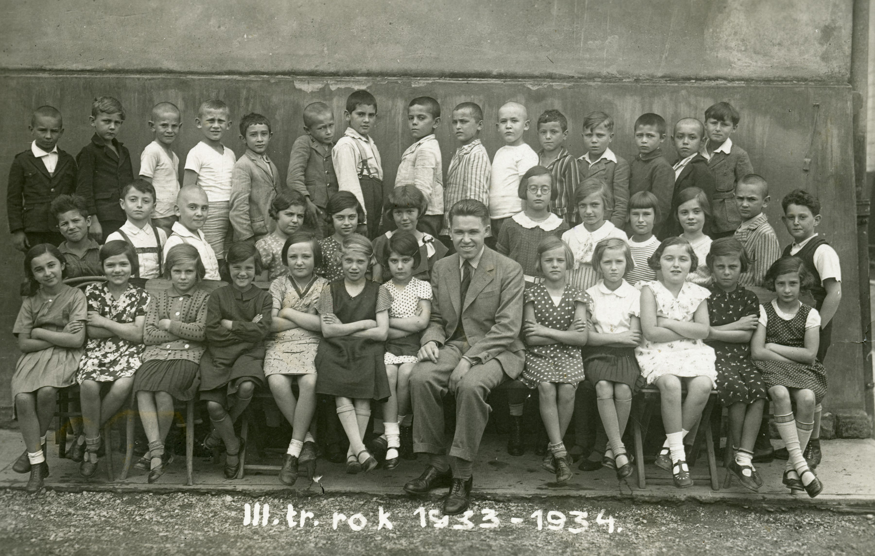 Children in the third grade of the Jewish elementary school in Zilina.  Among those pictured is the teacher Simon Goldberger (later Golan) and Bandi Jaacob Sigmund.   Liselote Stein is seated on the left.