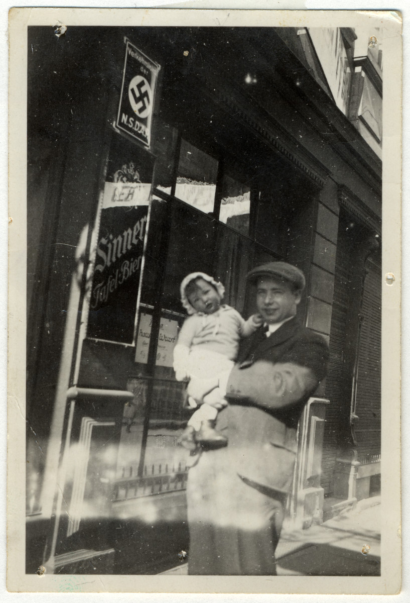 Leo Kaelberman holds his daughter Ellen outside a business in Mannheim, Germany adorned with a Nazi poster.