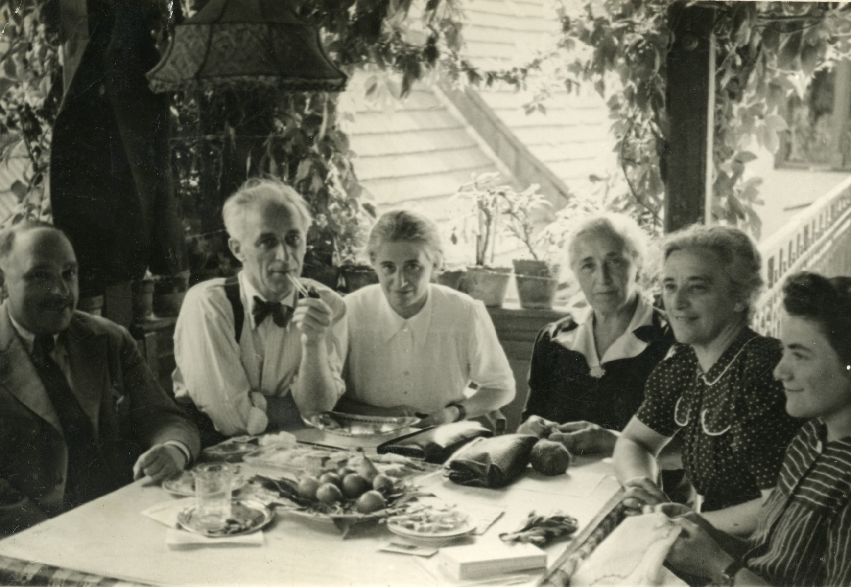 Members of the Duschnitz family sit around a table laden with fruit.  Pictured are Erno Duschnitz (donor's maternal uncle), Leonka Duschnitz Porgesand her husband Max Porges (donor's maternal aunt and uncle) , Malvin Duschnitz Kurti (another maternal aunt) and Frida Duschnitz Sigmund.