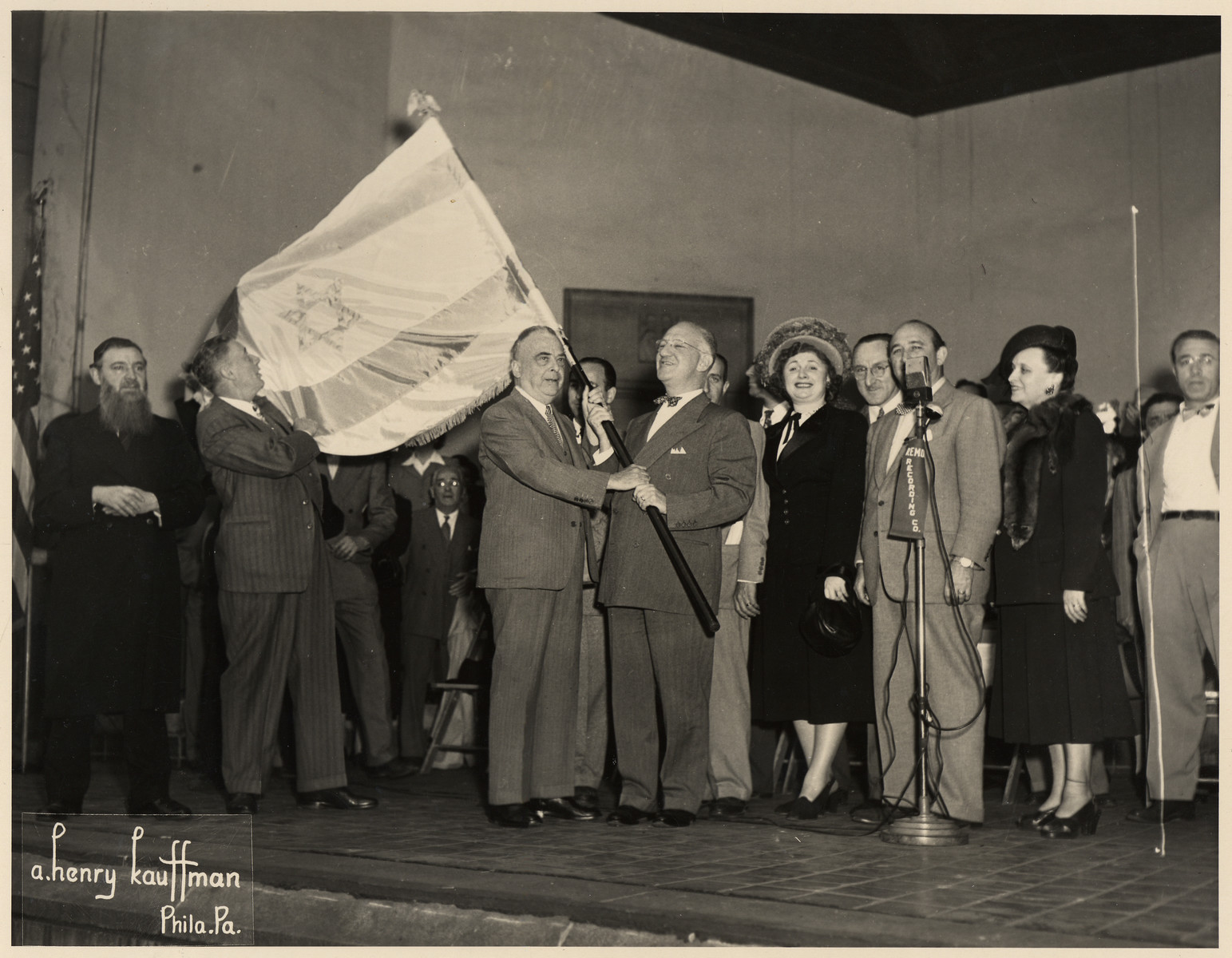 The  Israeli flag is held aloft at a ceremony in Philadelphia, held shortly after the Israeli declaration of Independence.  Among those pictured are (left to right):  George Louis (holding the flag), Philadelphia Mayor Bernard Samuel and Judge Levinthal (both holding the flag pole), Lawrence G. Horowitz (the donor's grandfather, behind Judge Levinthal), and Ann Sebotnik (the donor's aunt).