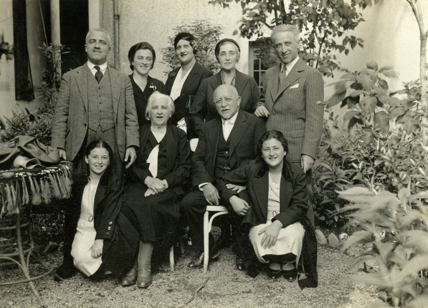 Family portrait of the Duschnitz family in a garden in Piestany.   Pictured standing are Robert Duschnitz (brother Frida Sigmund), Rozsi Duschnitz Erdelyi (sister of Frida Sigmund), Stefi Dushnitz (wife of Erno), Anna Duschnitz Diamant, and Erno Duschnitz.  Seated are Heda Erdelyi, Cecilia and Benedikt Baruch Duschnitz, Magda Erdelyi.