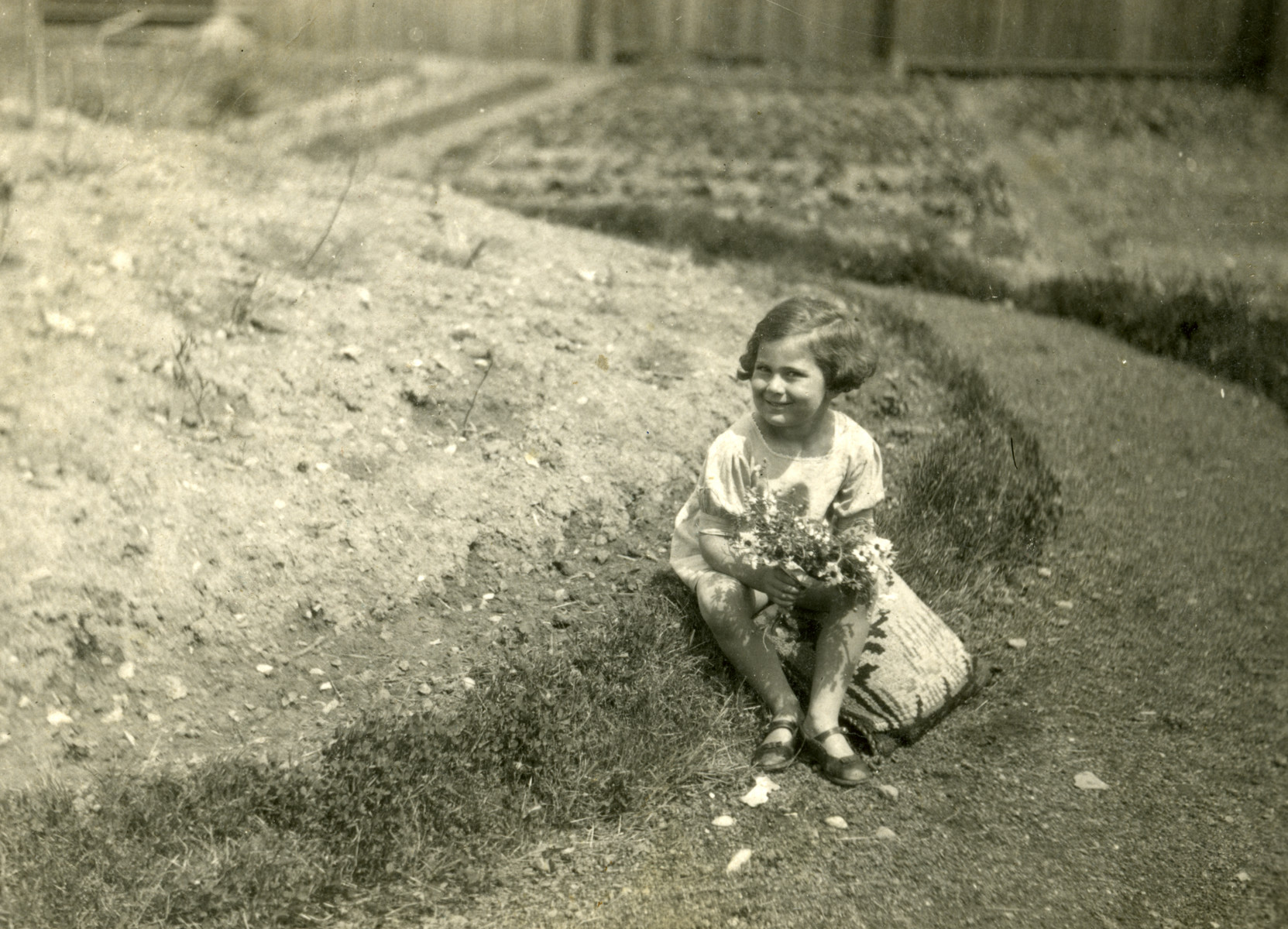 Suzanne Sigmund sits by a path holding a bouquet of flowers.