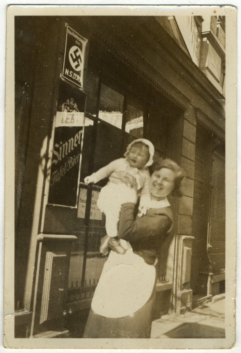 A German nanny holds Ellen Kaelbermann outside a business in Mannheim, Germany adorned with a Nazi poster.