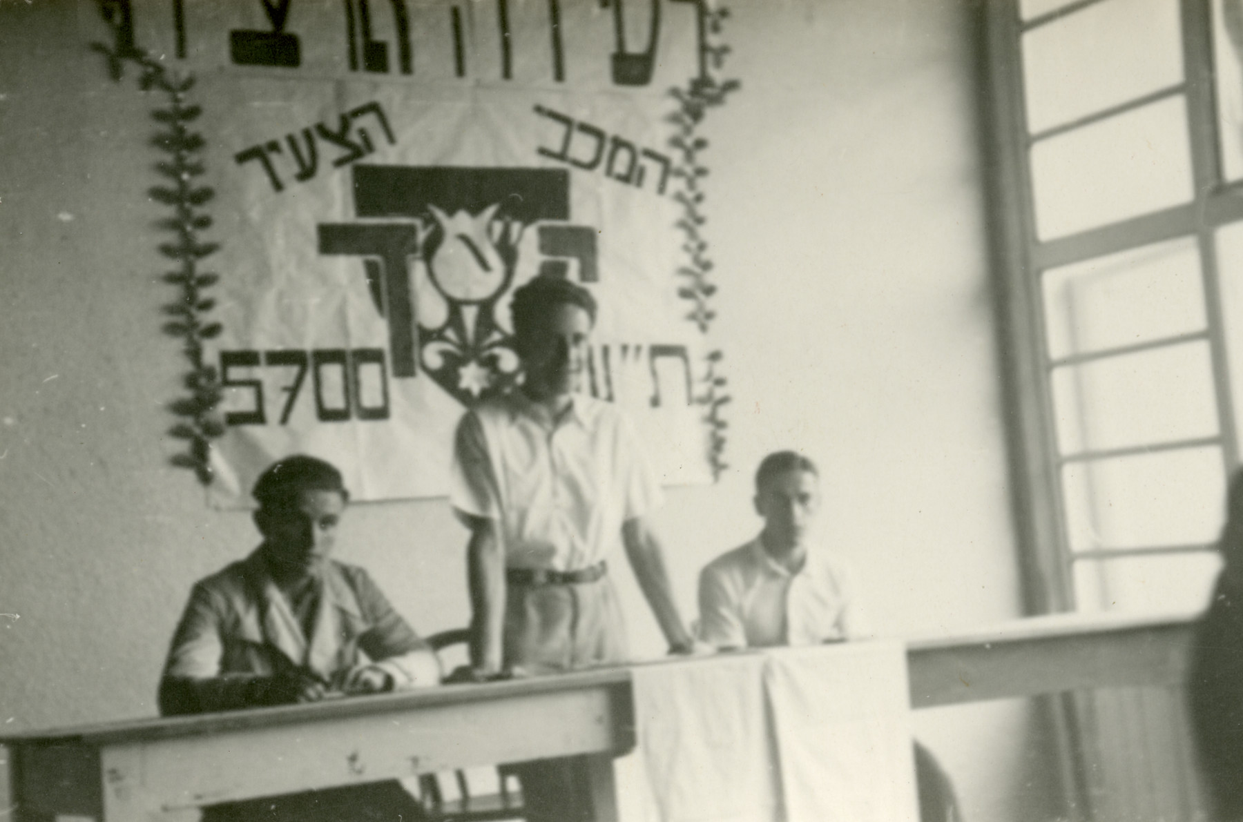 Leaders of the Maccabi team hold an opening ceremony in their summer camp in Czernohorske Kupele.  Pictured from left to right are Peretz Revesz, Eli Sajo and [possibly Josef Berger].