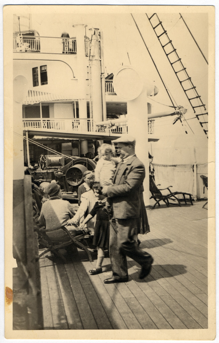Leo Kaelbermann walks on the deck of a ship bound for the United States with his two young daughters.