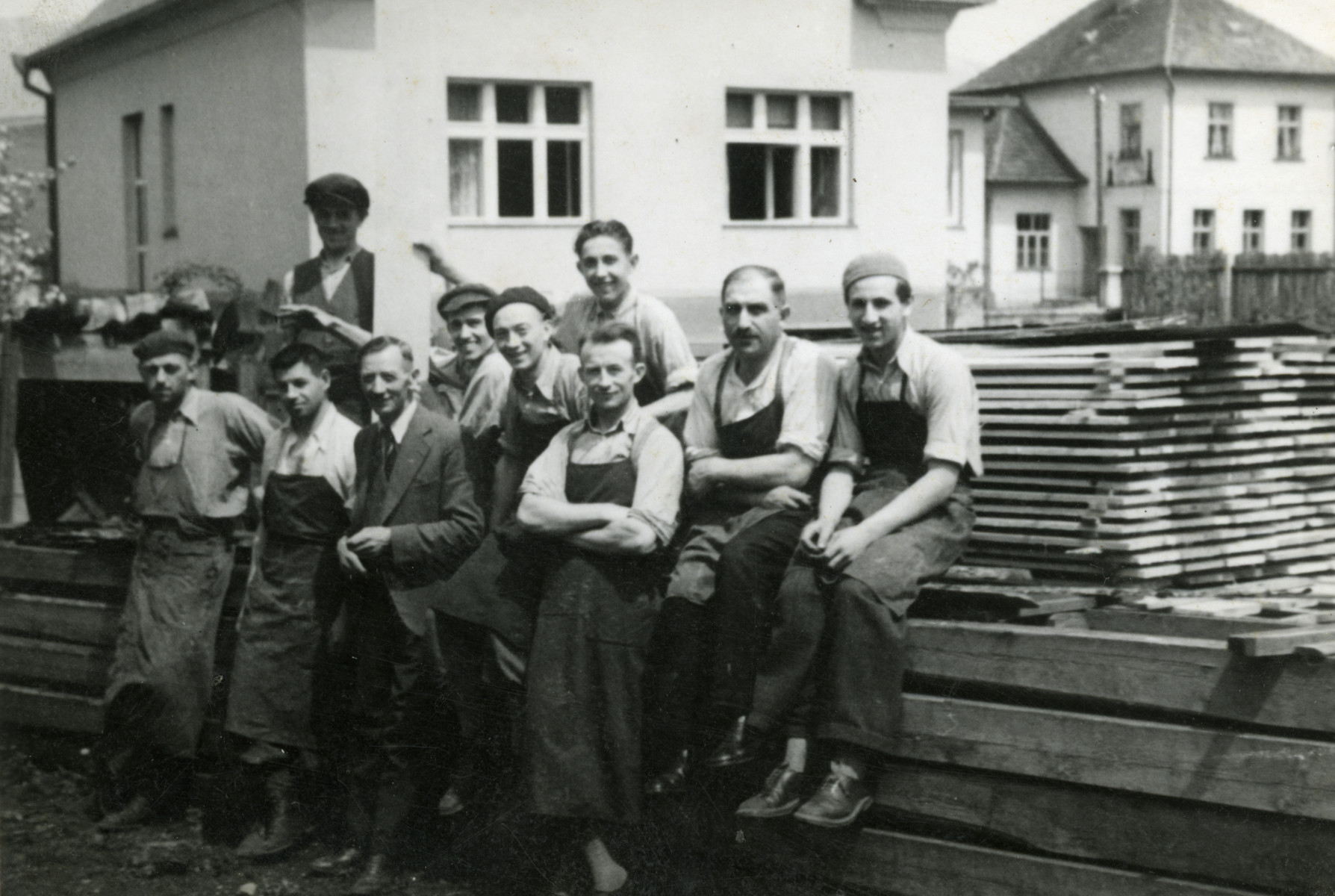 Jewish workers [probably in the Novaky camp] pose outside the wood workshop.