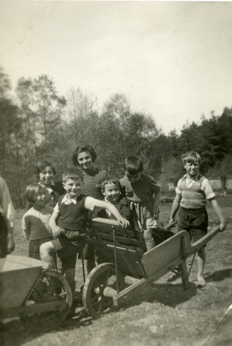 A group of young children play with a wheelbarrow on the grounds of the Chaumont children's home.