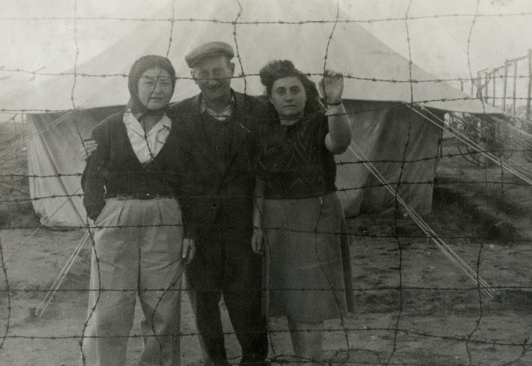 Three refugees in Cyprus who were refused entry into Palestine look out through the barbed wire fence.