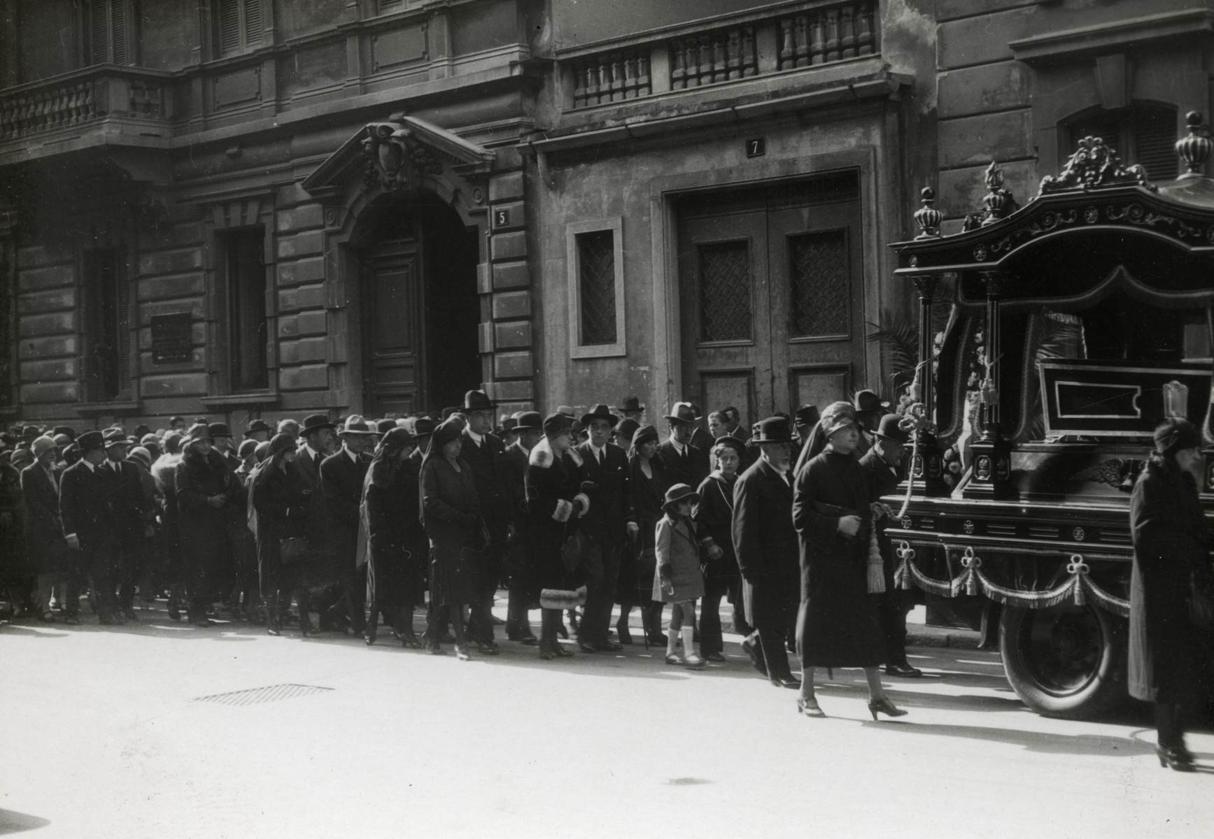 A procession walks down a street of Milan during the funeral of Eliza Navarra (Dario's grandmother).