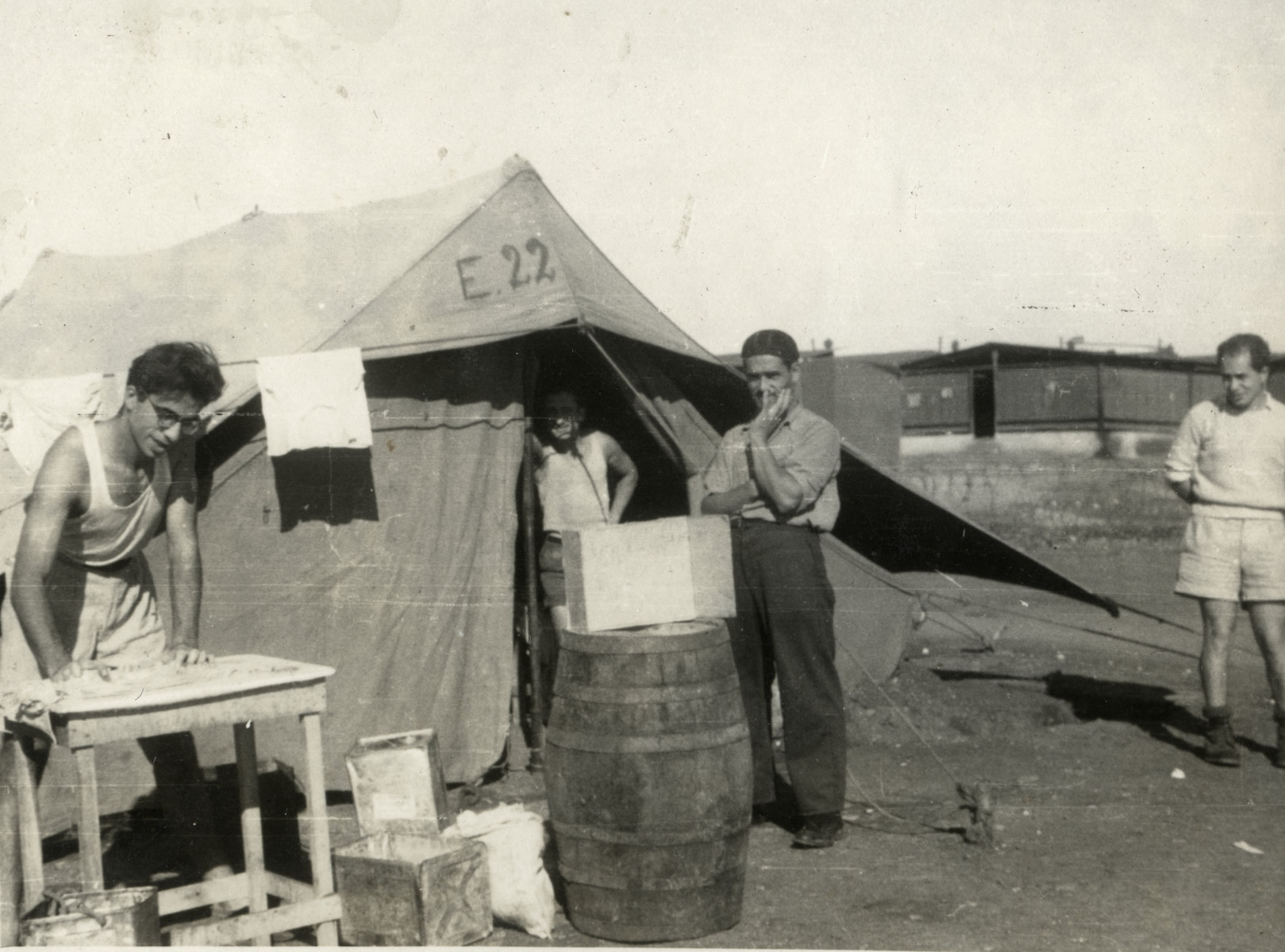 Dario Navarra, Giacomo Muttarazzi, and Moshe Dana work in front of their tent in a detention camp in Cyprus.
