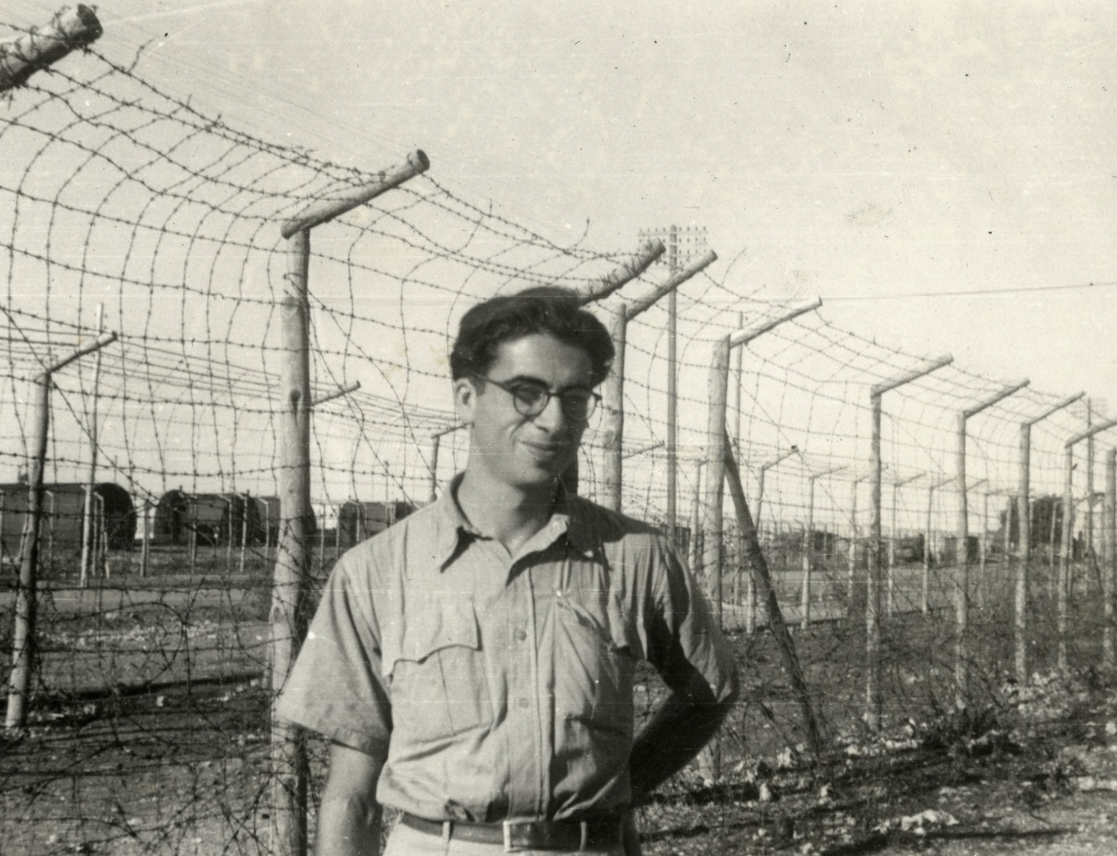 Dario Navarra poses in front of the barbed wire fence in the refugee camp in Cyprus.