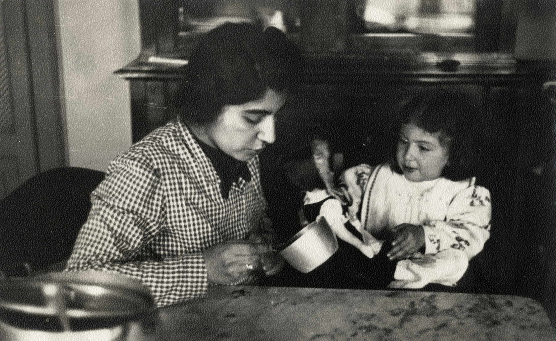 Ada Nissim sits with her young daughter Leah in their kitchen in Trieste.