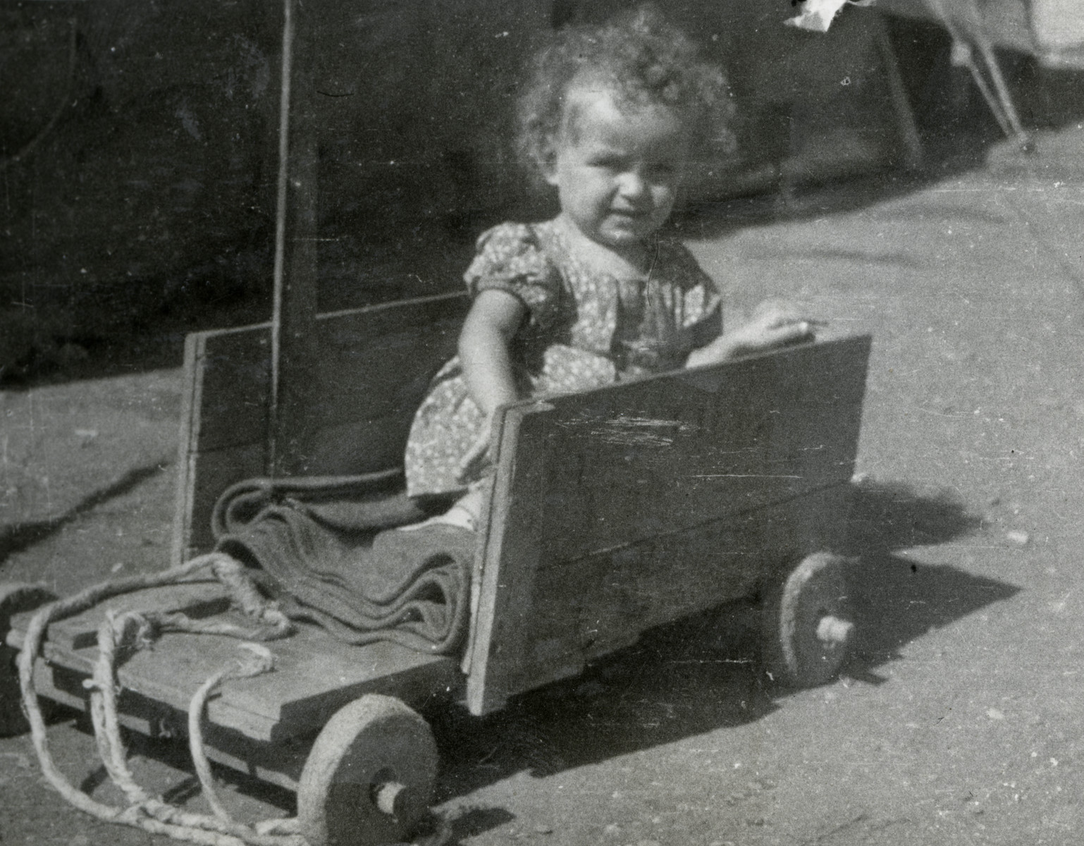 Close-up portrait of a young child in a toy cart in the Cyprus internment camp.