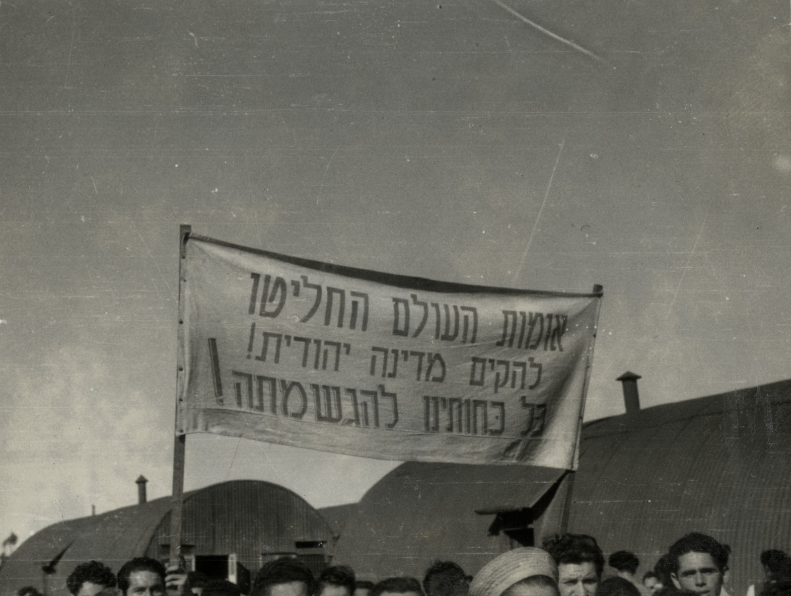 """Refugees in Cyprus celebrate the United Nations Partition Plan for Palestine; the sign says that the U.N. decided to create a Jewish state.   The banner reads """"The nations of the world decided to establish a Jewish State.  All our strength is for fulfilling it!"""""""