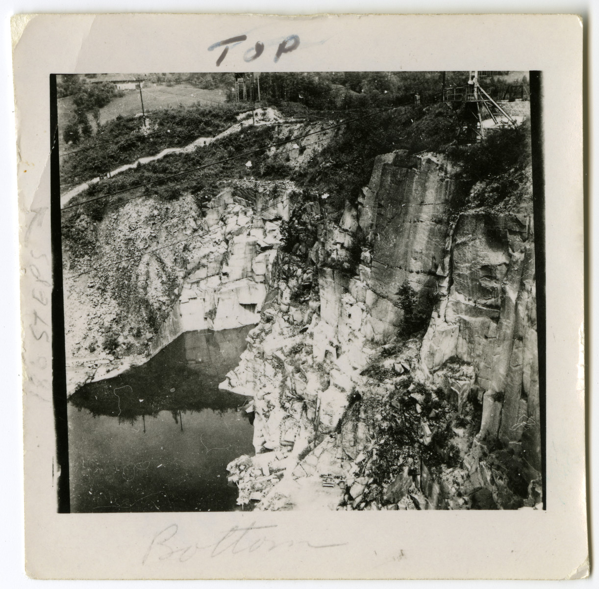 "View of the stone quarry where prisoners carried heavy stones up a tall stairwell.  Original caption reads: ""This is the 186 steps Nazis made prisoners half starved carry heavy loads up that white path on the left.  If they couldn't make it they whipped them.  The cliff is where they pushed them off."""