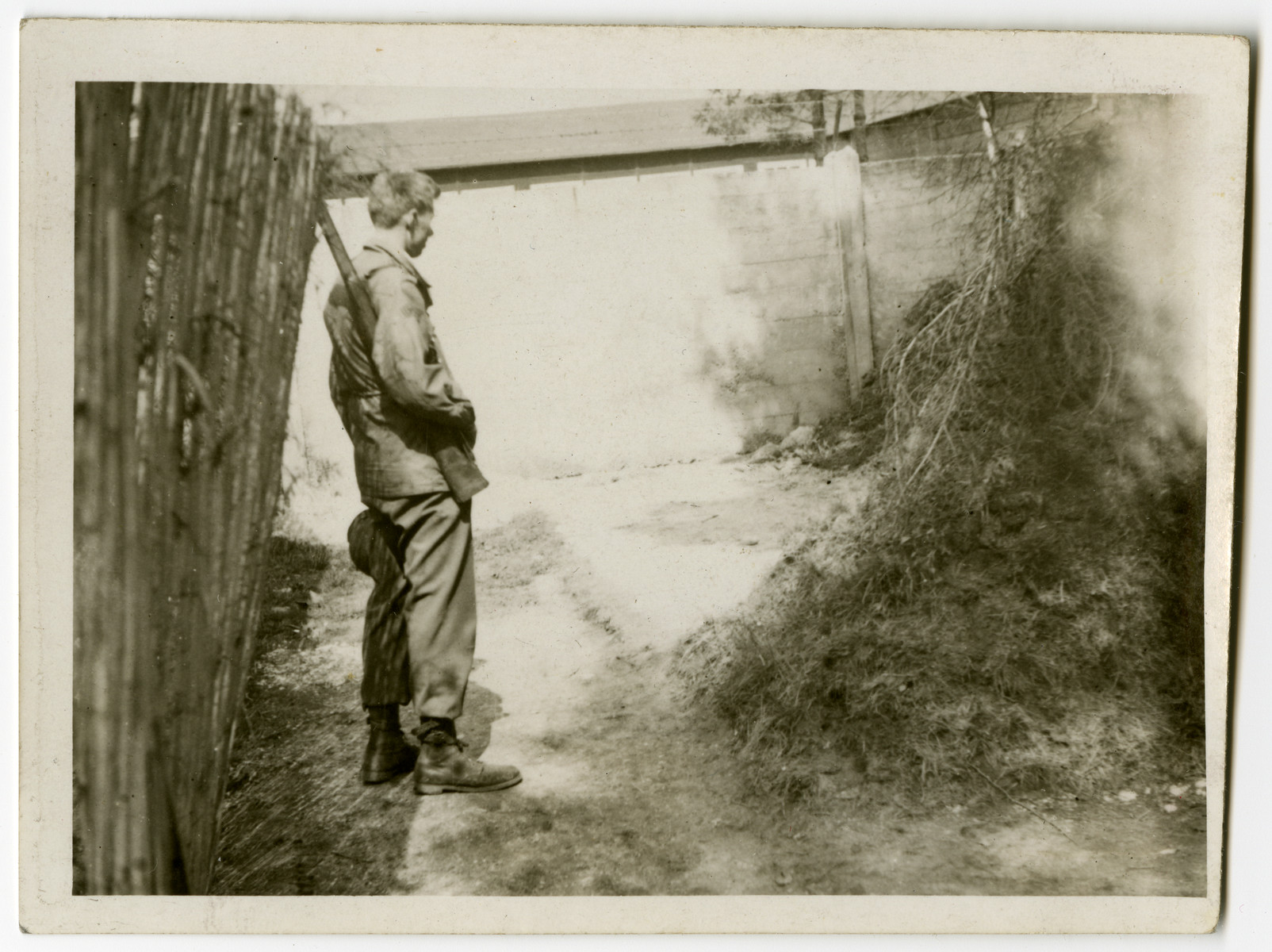 """U.S. soldier Clarence E. Alberg inspects an execution site in the Dachau concentration camp.  The original caption reads: """"I was looking at the place where the women were shot."""""""