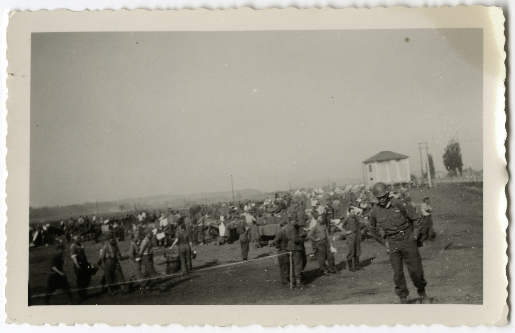 An American soldier guards German prisoners of war in a POW camp.