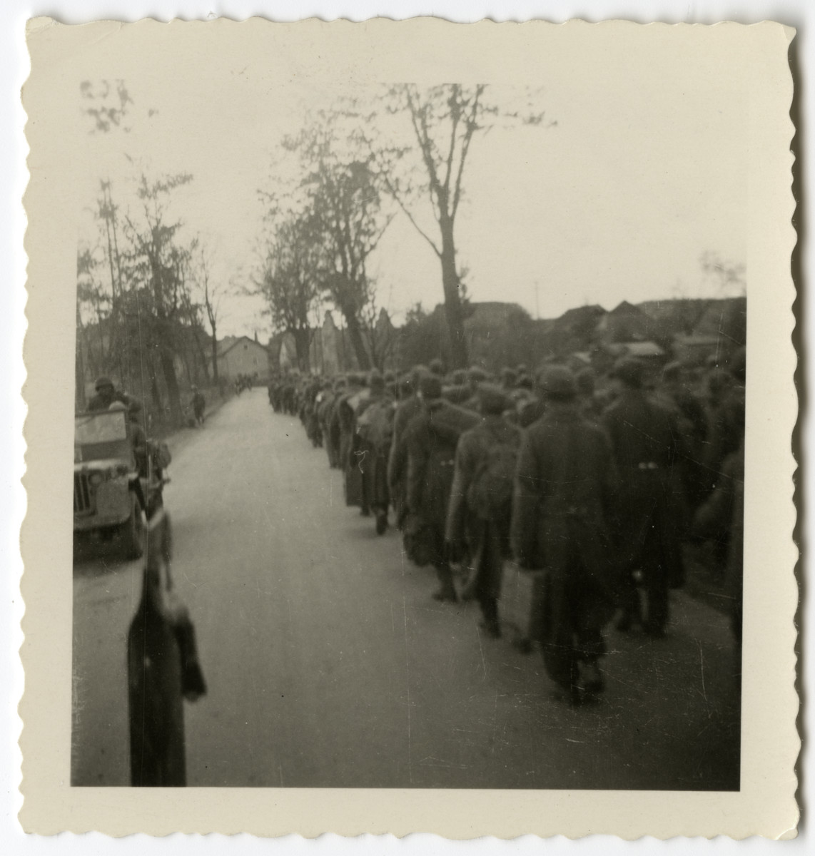 German POWs, captured by the American 261st Regiment, march down the road of an unidentified village.