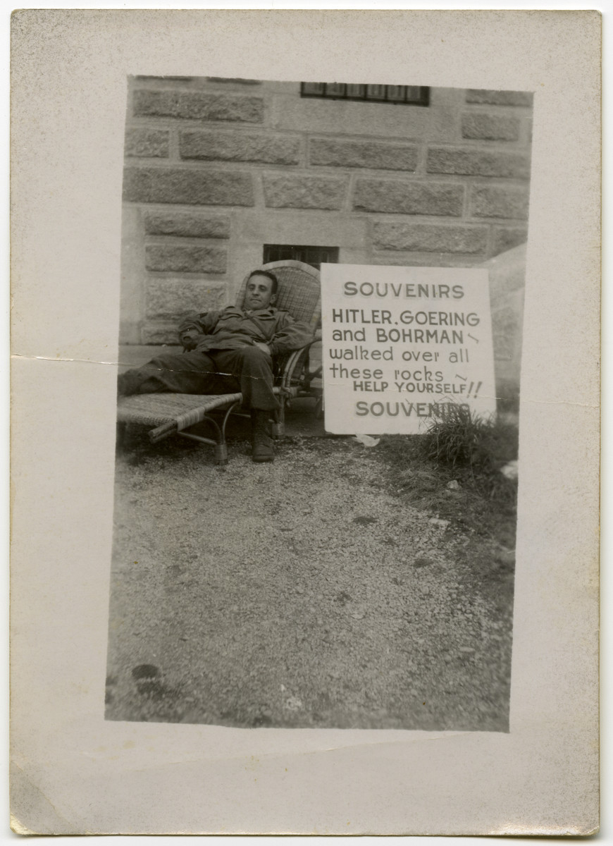 """American Jewish soldier Jack Postman relaxes outside in a lounge chair in front of a sign that reads: """"Souvenirs: Hitler, Goering and Bohrman walked over all these rocks. Help yourself!"""""""