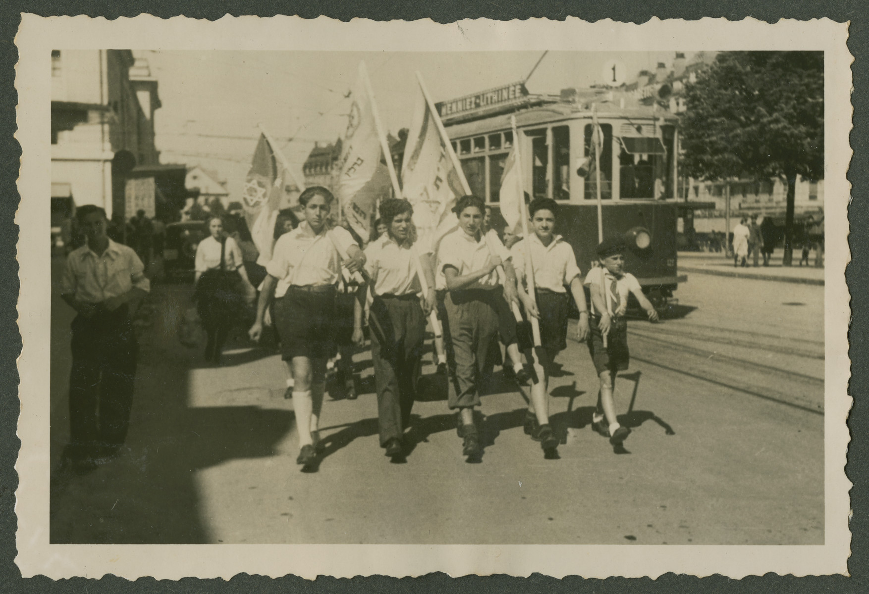 Zionist youth carrying flags parade through a street in Switzerland.