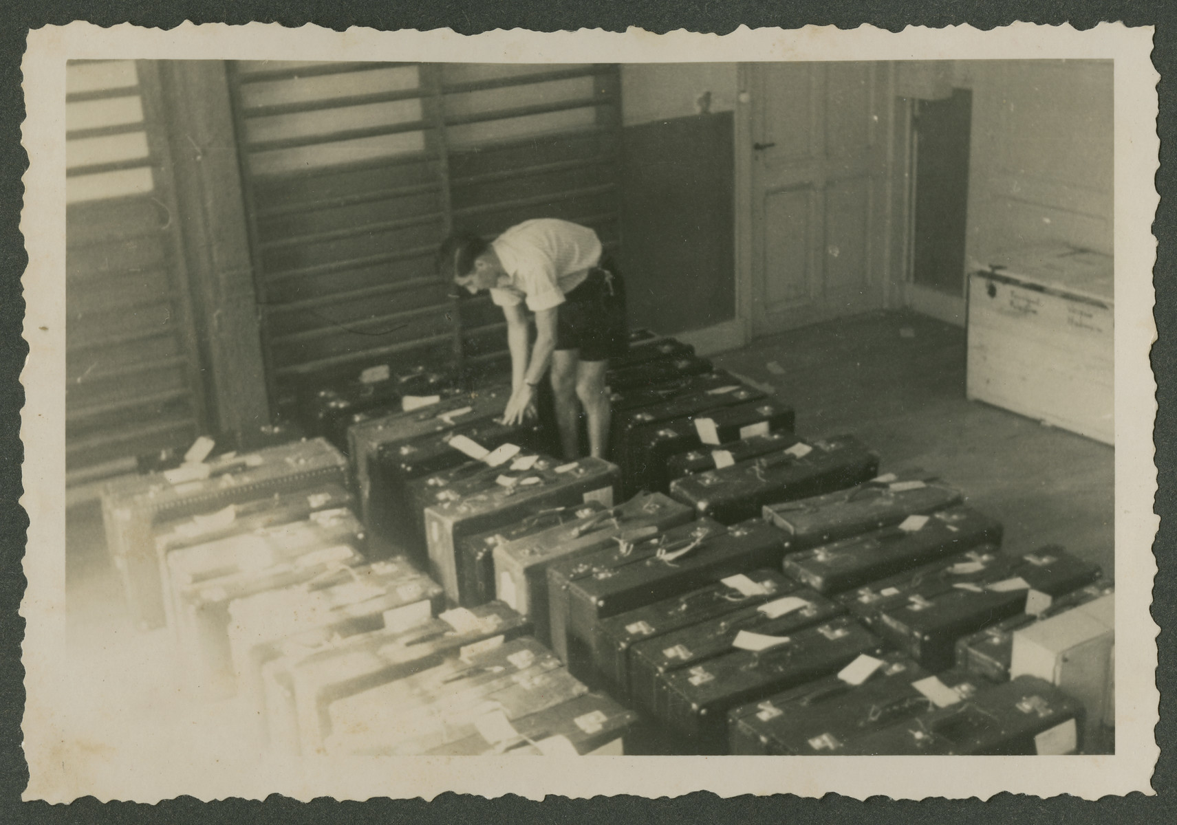 A teenage boy organizes rows of suitcases in preparation for the departure of a group of Zionist youth to Palestine.