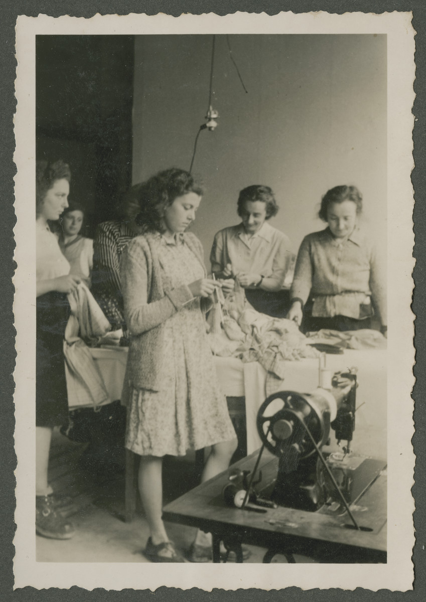 Teenage girls sort and sew clothing in a Zionist children's home in Switzerland.