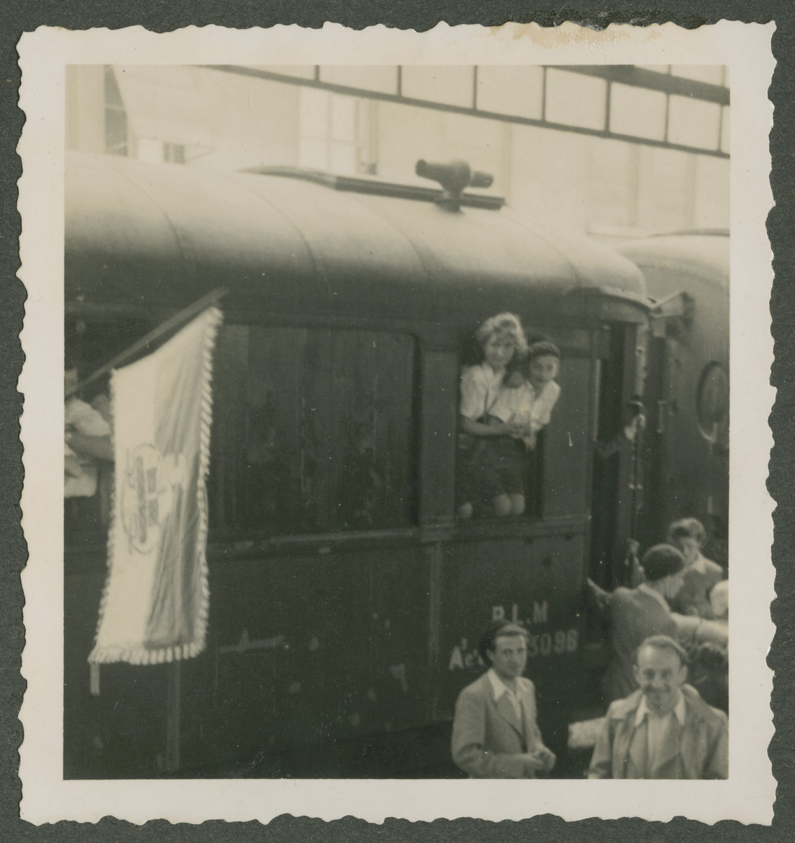 Children from a Zionist children's home in Switzerland, lean out a train window [probably during the first leg of their immigration to Palestine.]